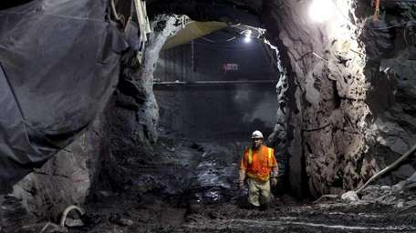 A construction worker walks in a tunnel between