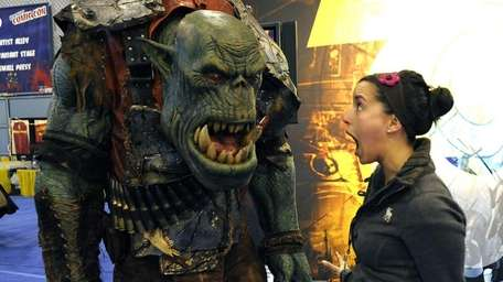 A convention attendee stands next to Ork from