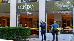 Police investigate the scene at London Jewelers in