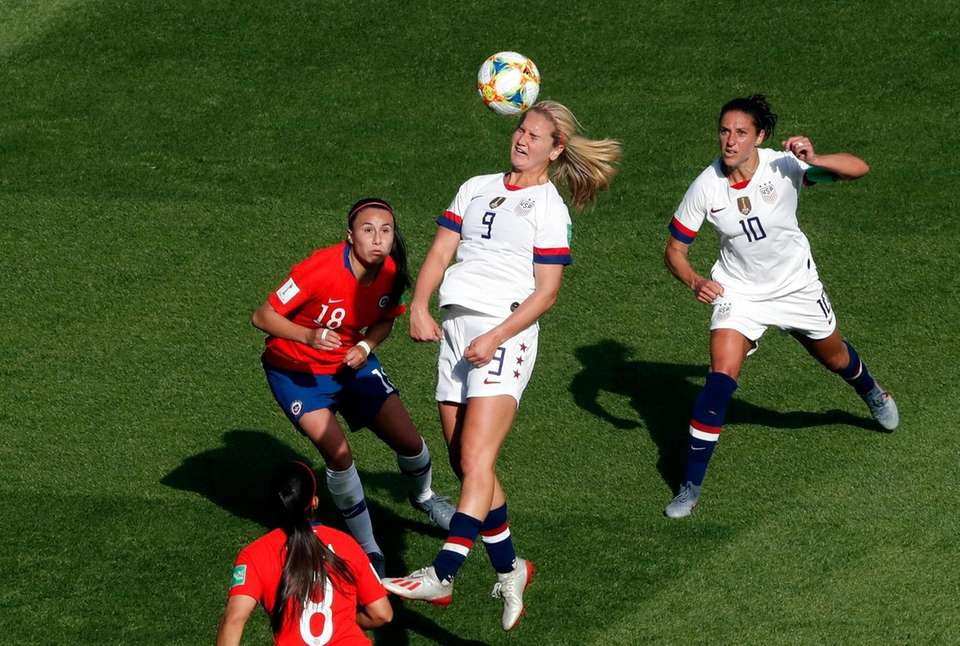 United States' Lindsey Horan, center, heads the ball