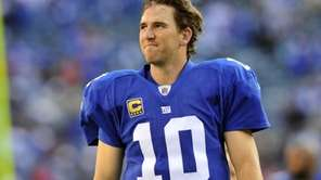 Eli Manning smiles as he walks off the