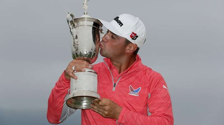 Gary Woodland posses with the trophy after winning
