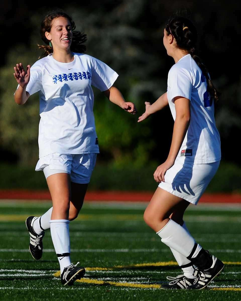 Kellenberg's Amanda Calzolano, left, gets congratulated by teammate