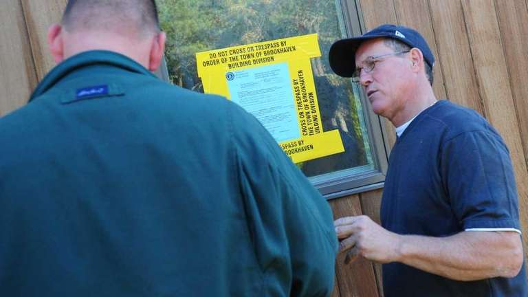 Tom Busiello, right, speaks with a Town of