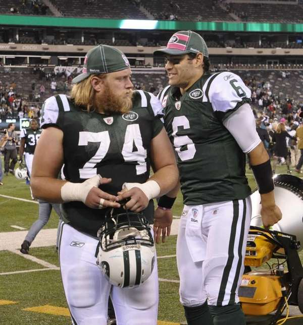 Mark Sanchez stands next to Nick Mangold during