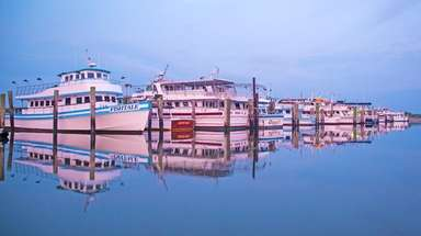 Fishing boats are reflected in the water at