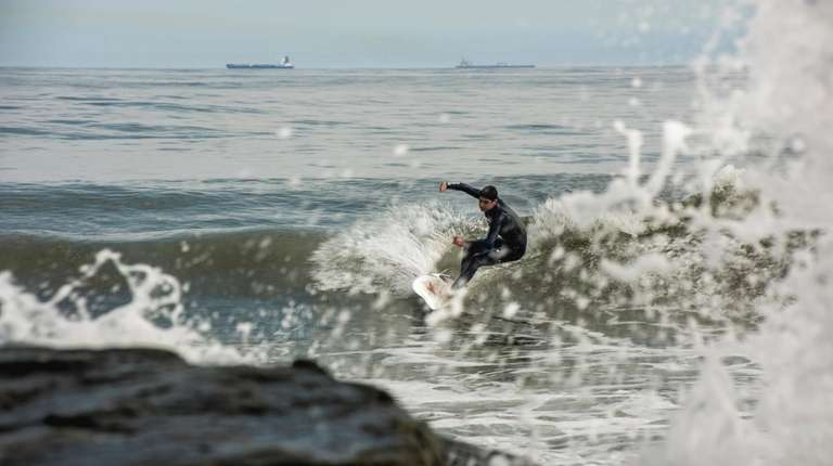 A surfer takes to the waters off Long
