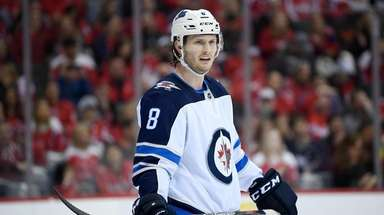 Jacob Trouba (8) stands on the ice during