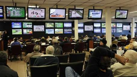 Players watch the first race at Aqueduct at