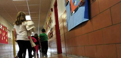 A first-grade class returns to their classroom at