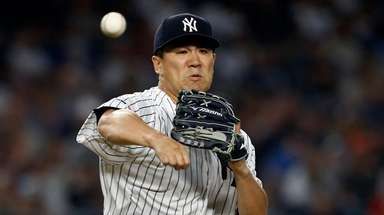 Masahiro Tanaka, firing to first base, pitched a