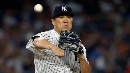 Masahiro Tanaka, firing to first base, pitched a
