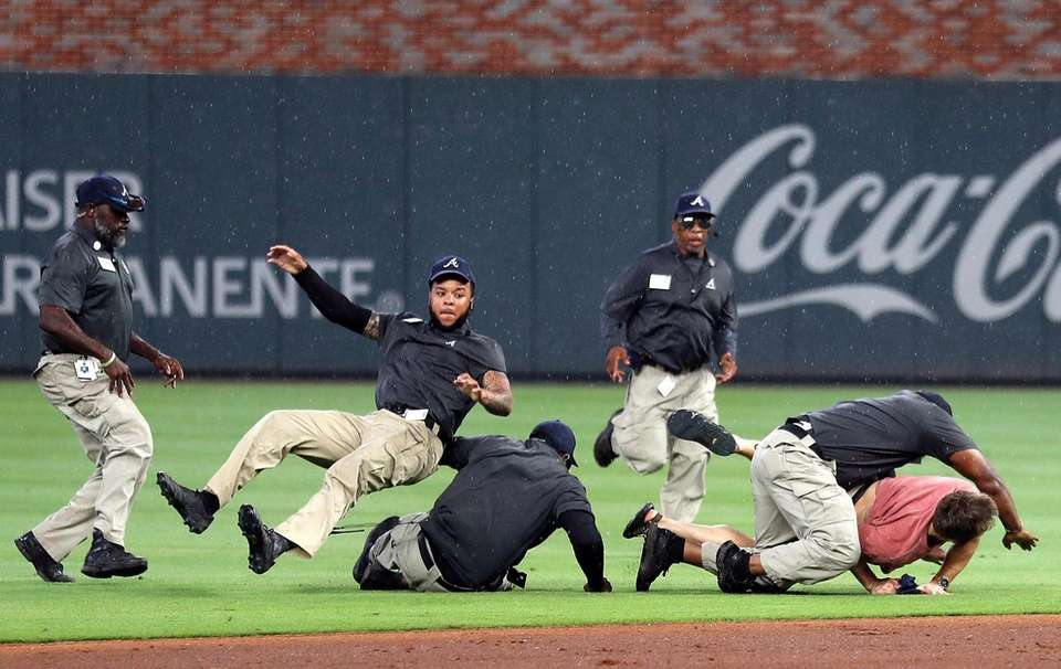 Members of Atlanta Braves security staff tackle a