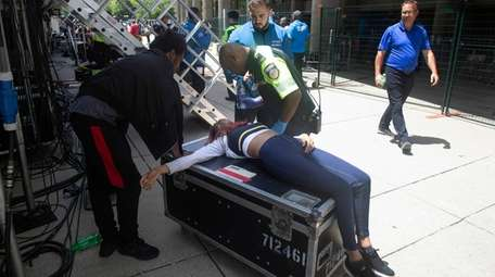 A woman is treated by a paramedic after