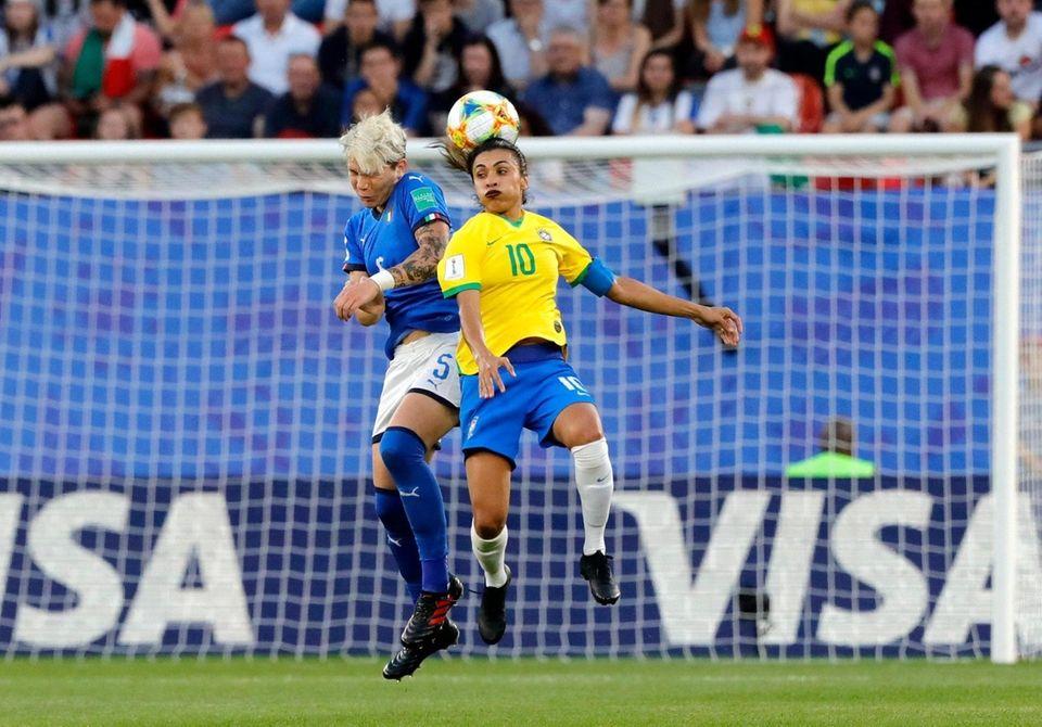 Italy's Elena Linari, left, jumps for the ball