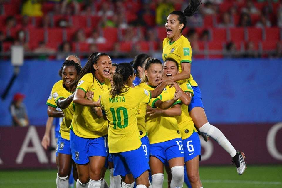 Brazil's forward Marta (C) is congratulated by teammates