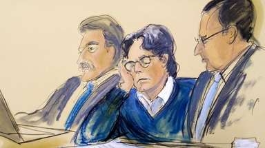 Defendant Keith Raniere, center, sits with attorneys Paul