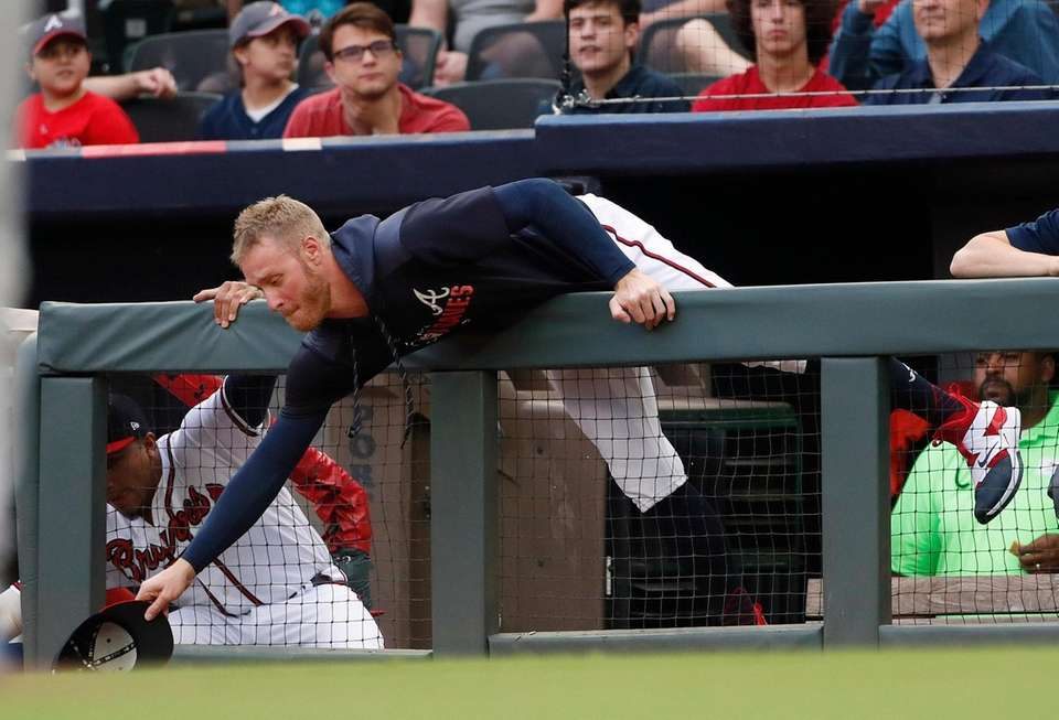 Braves pitcher Mike Foltynewicz reaches over the dugout
