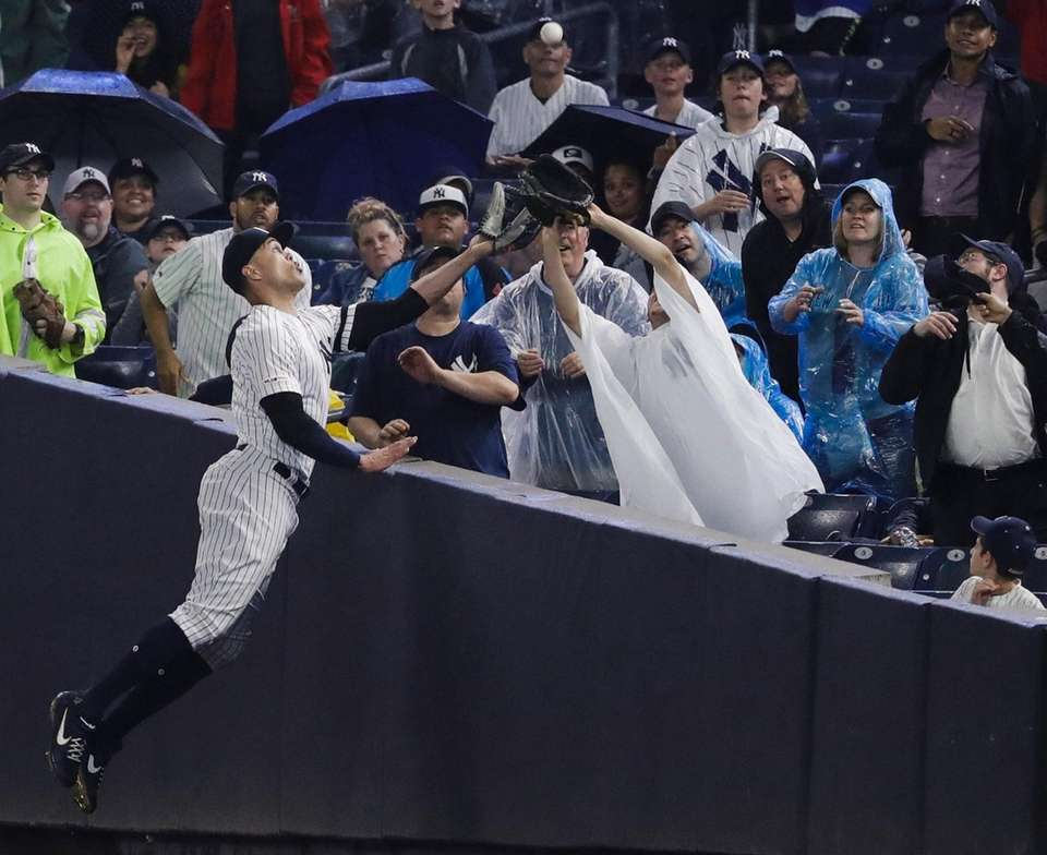 New York Yankees' Giancarlo Stanton leaps for and