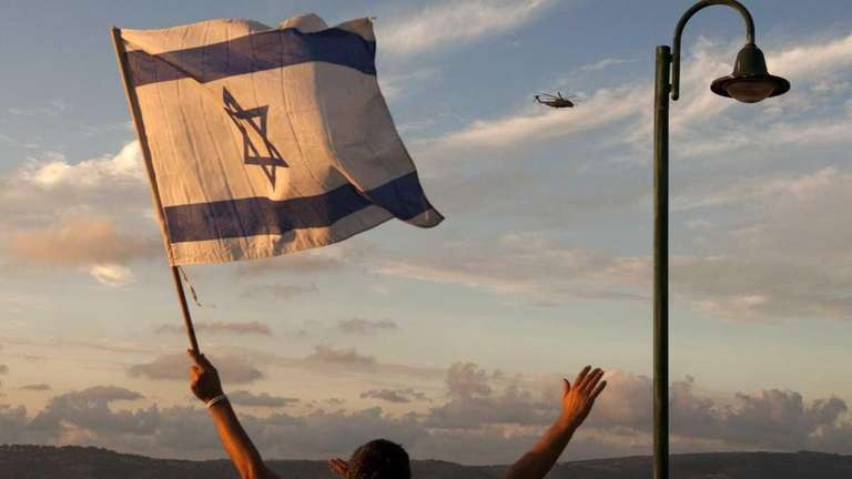 An Israeli waves as a helicopter transporting Israeli