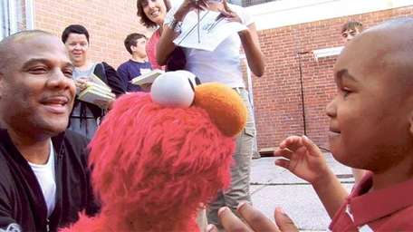 Kevin Clash, left, and Elmo entertain a young