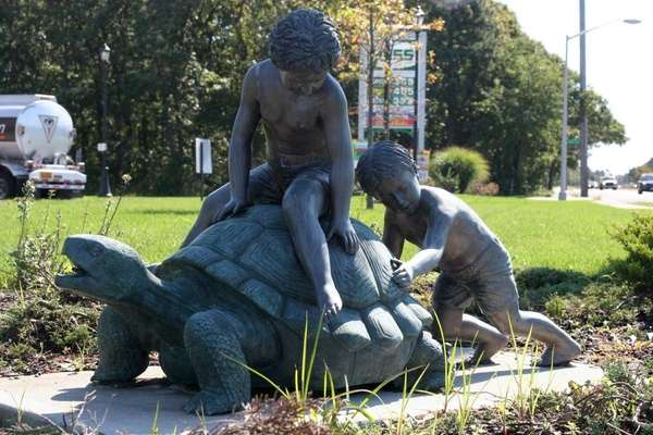 A statue of a boy pushing a turtle