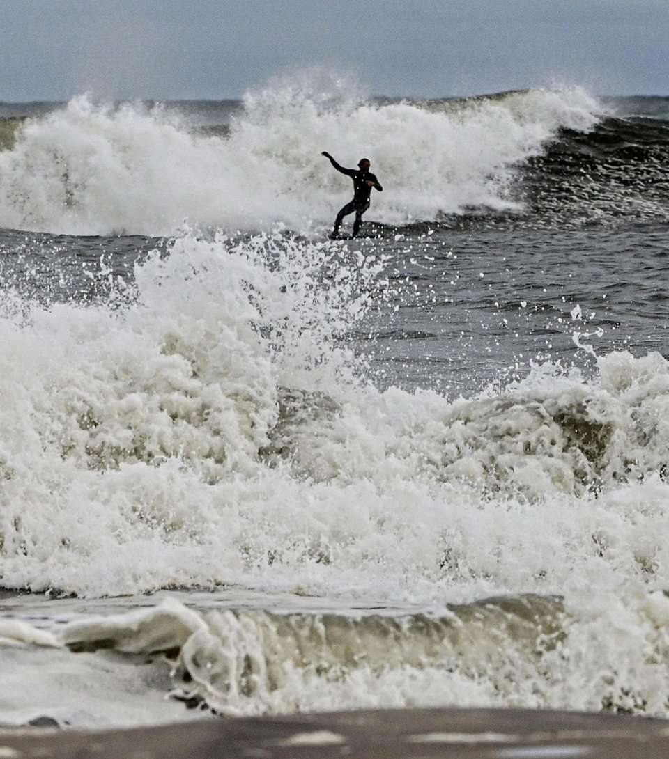 A surfer takes advantage of the high surf