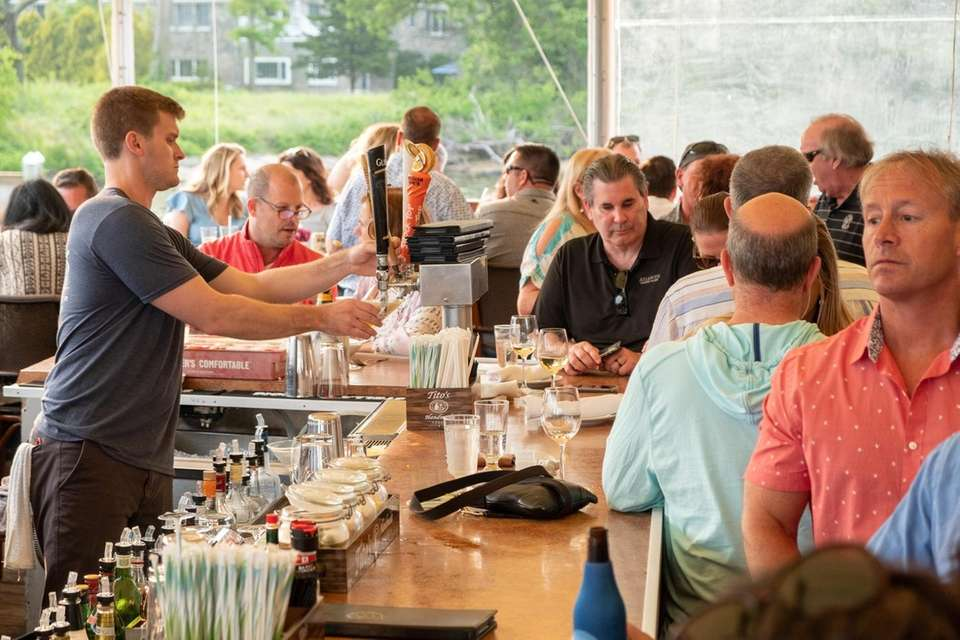 Patrons mingle at the bar and sip cocktails