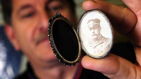 Auctioneer Philip Weiss holds a locket owned by