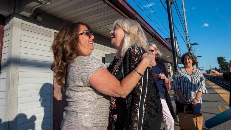 Linda Ficano, center,, greets Mary Musto, left, as