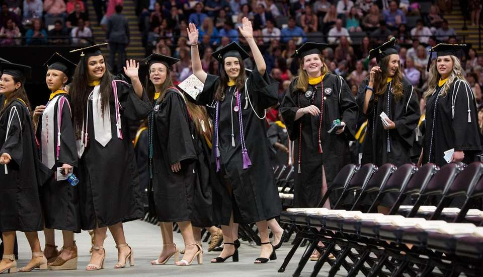 Graduates wave to family and friends as they