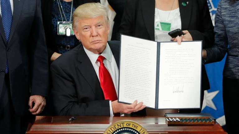 President Donald Trump holds up the executive order