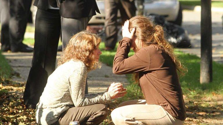 Catherine Desola, left, consoles her daughter, Karen Shriver