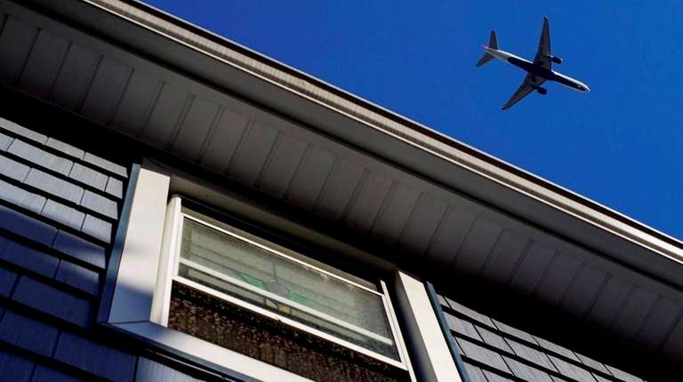 A large passenger jet passes over a home