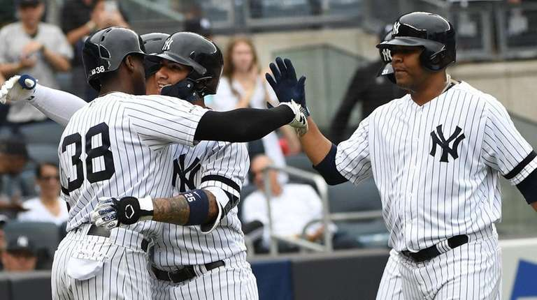 Yankees' Gleyber Torres is embraced by Cameron Maybin