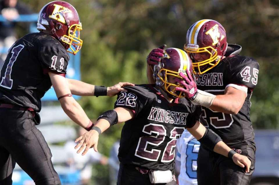 Kings Park's Tom Milich, center, celebrates a sack