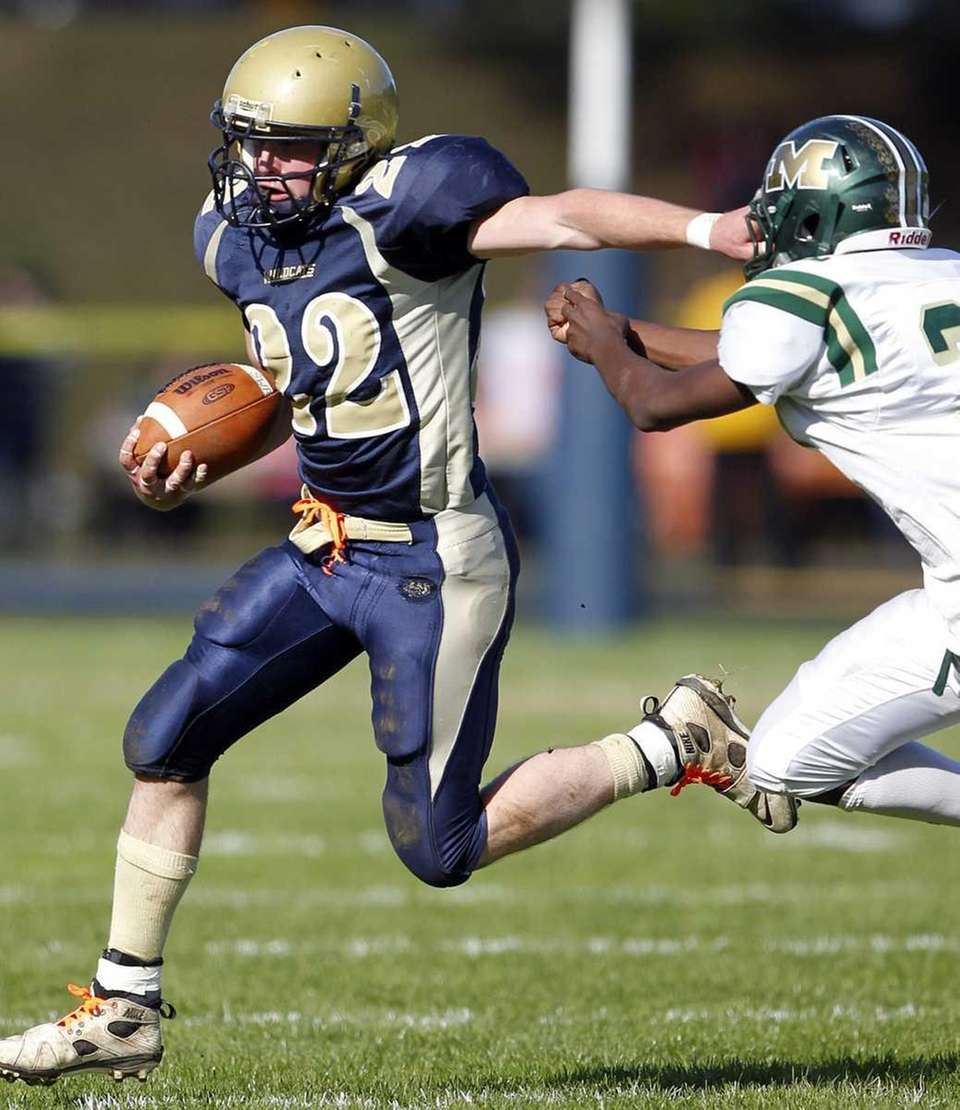 Shoreham's Dylan Bates (22) with the stiff arm