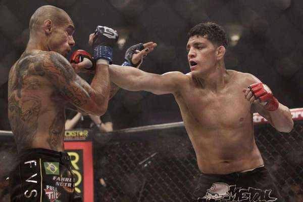 "Nick Diaz, right, punches Evangelista ""Cyborg"" Santos, from"