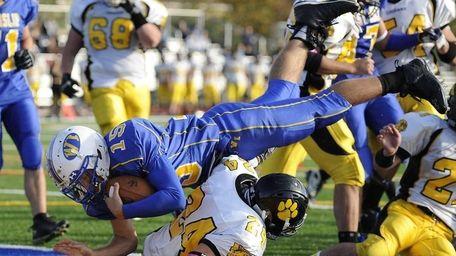 West Islip quarterback Anthony Santo,dives over Commack DB