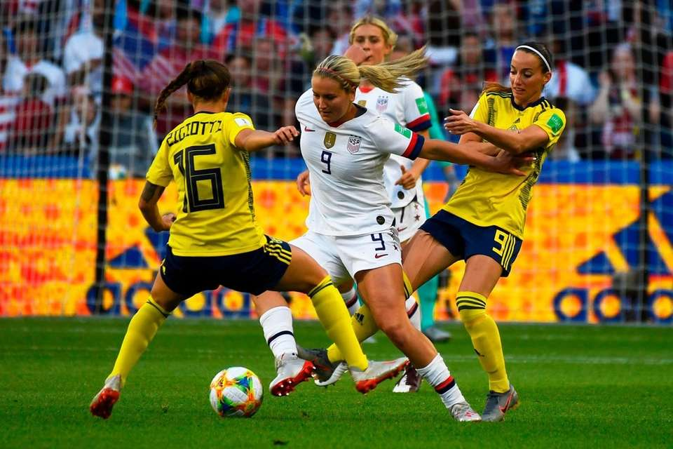 United States' midfielder Lindsey Horan (C) vies for