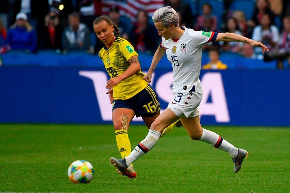 United States' forward Megan Rapinoe (R) vies for