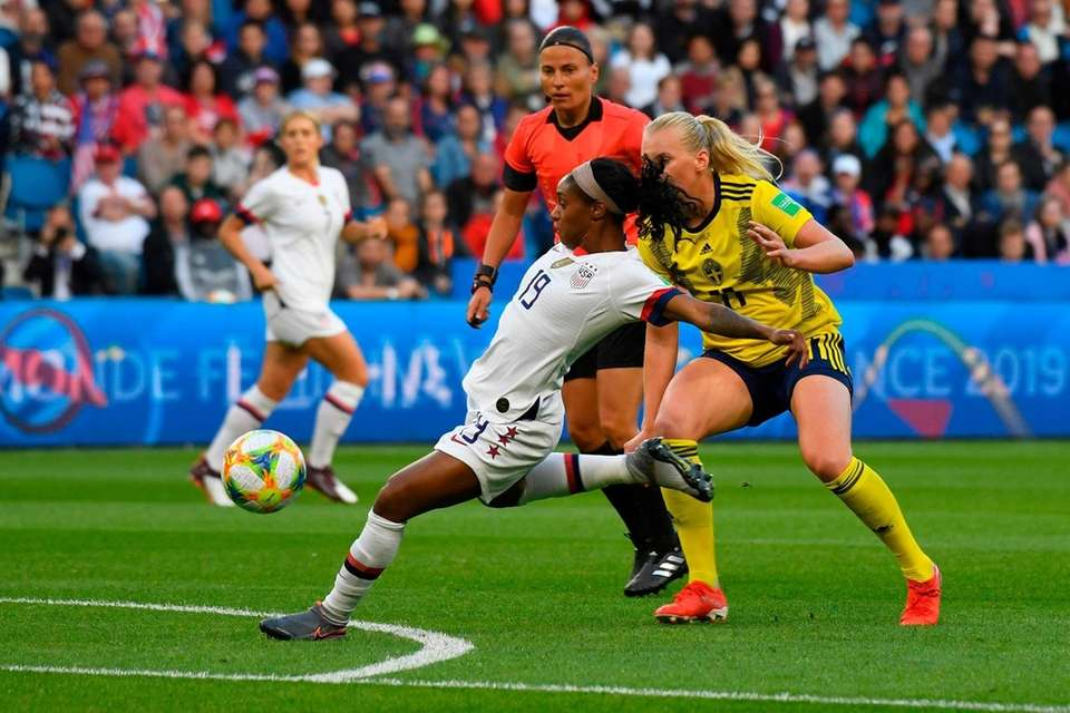 United States' defender Crystal Dunn (L) kicks the