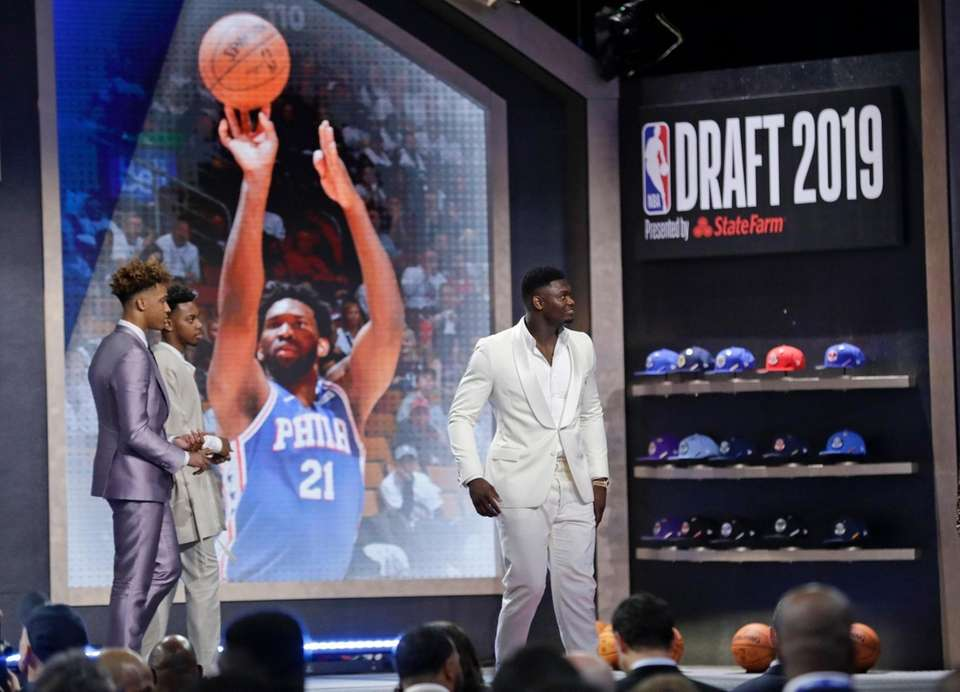 Duke's Zion Williamson, right, leaves the stage after