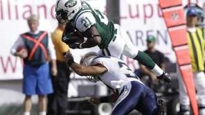 New York Jets' LaDainian Tomlinson, top, jumps with