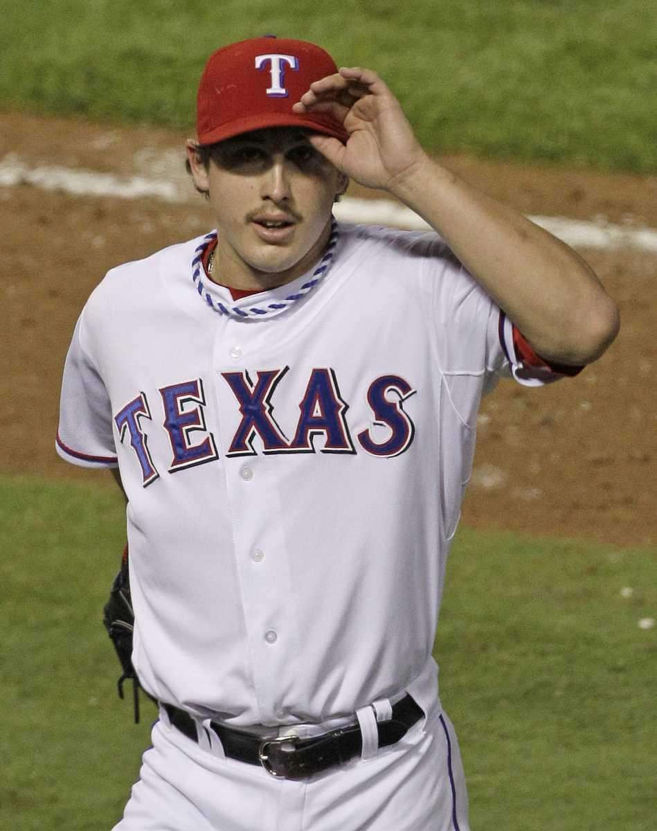 Texas Rangers starting pitcher Derek Holland waves to