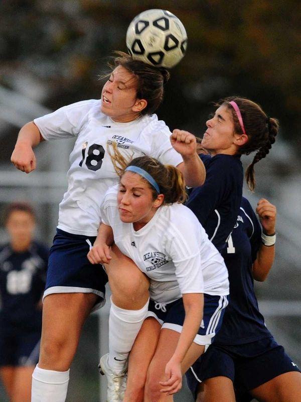 Oceanside High School's Danielle Rossi, left, leaps for