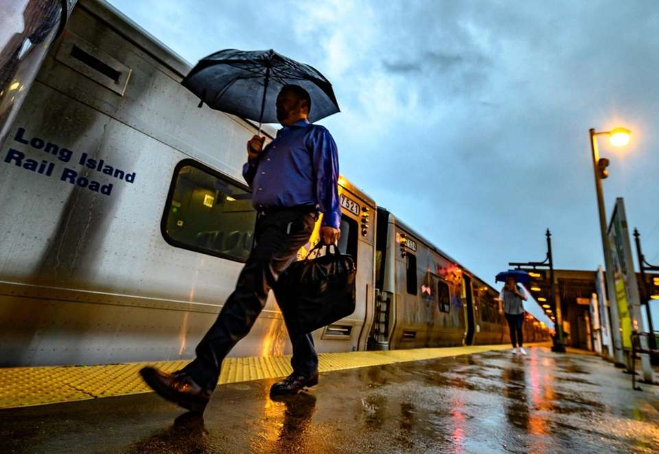 6:28 a.m. Commuters take cover from the rain
