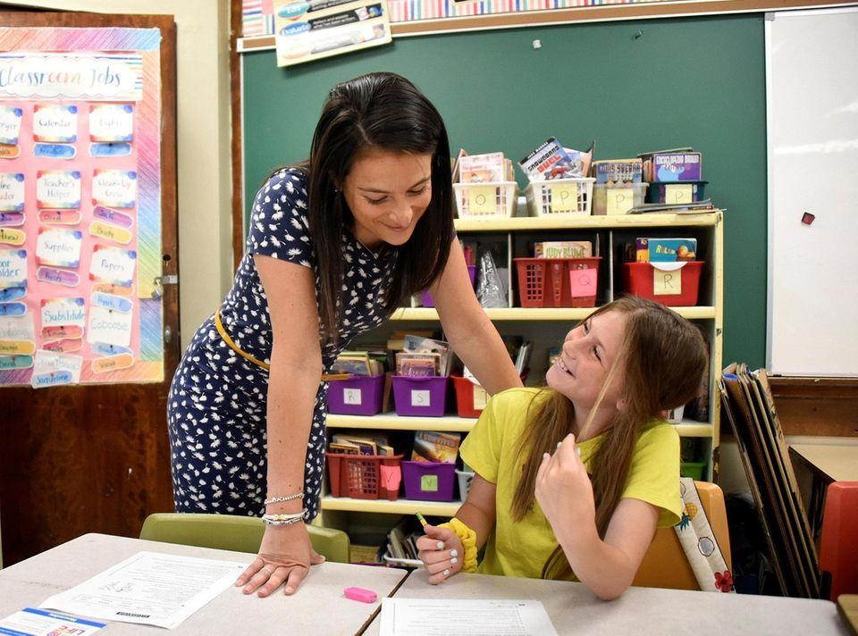 9:30 a.m. Roseann Malizia helps student Alex Backlin,