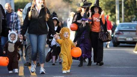 Kids and parents in variety of costumes walk