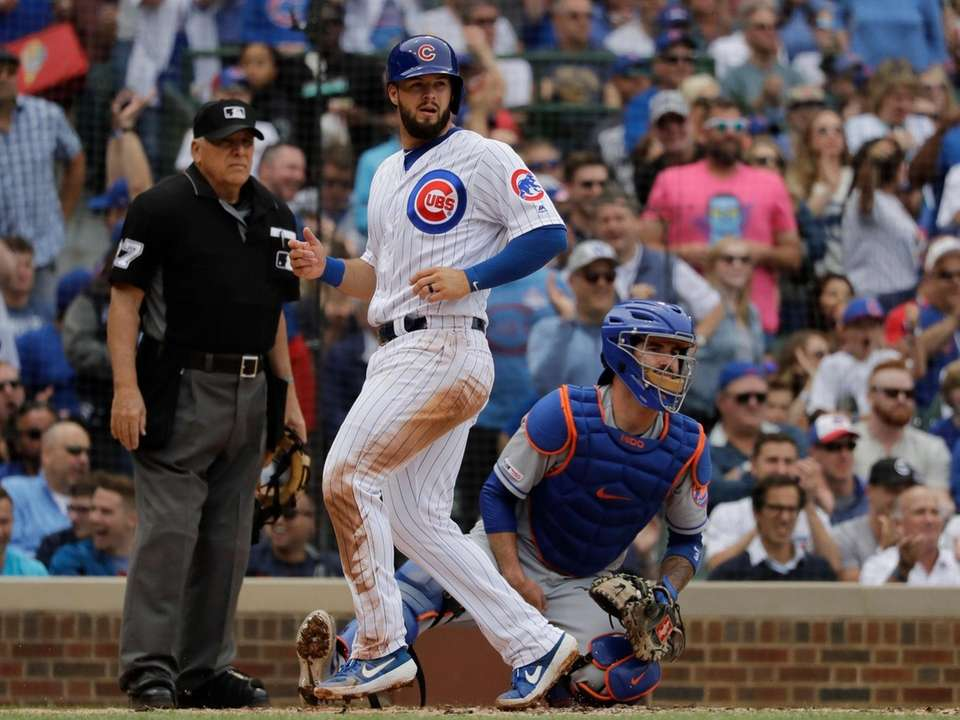 Chicago Cubs' David Bote, left, scores on a